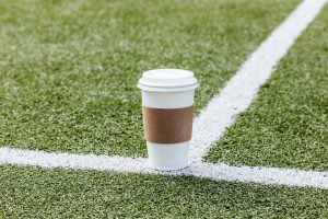 Blank coffee paper cup on football field