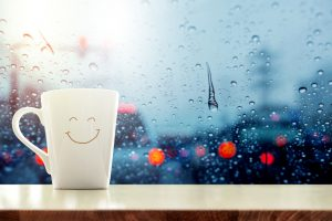 Happy Coffee Mug with smilely face on desk inside glass window, Blurred traffic jam light in city as outside view, Relaxing in cafe on rainy day