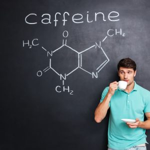Handsome young man drinking coffee over blackboard background with drawn chemical structure of caffeine molecule