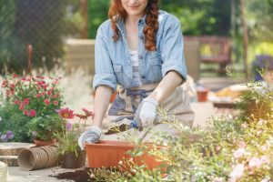 Red haired woman pouring soil into container for planting flowers during gardening work on terrace