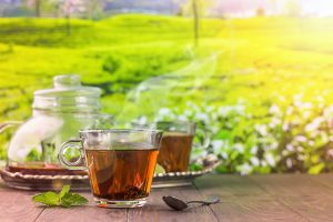 Tea in a glass cup on the wooden table and the tea plantations background