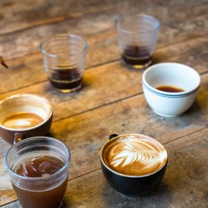 Different cups of coffee on wooden table, top view, vintage style