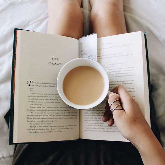Vemos las piernas de una mujer recostada que en su regazo tiene un libro abierto, porque está inmersa en su lectura mientras degusta un delicioso café con leche que también la ayuda a mantener la página abierta.